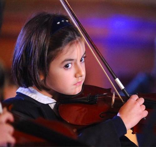 交响乐队中的意大利儿童为演唱者伴奏